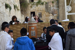Women relatives of a 13 year old boy celebrating his bar mitzvah ceremony at the Western Wall peer over the separation barrier between men and women worshipers.
